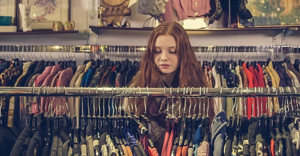 A young woman browsing at a thrift store